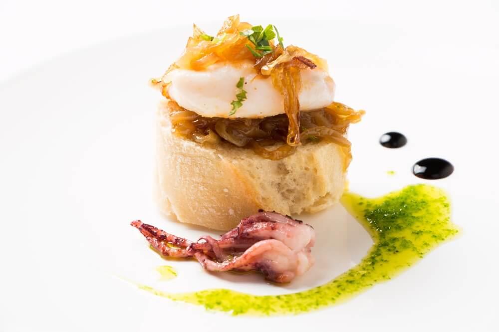 Pintxo van inktvis en gekarameliseerde ui, met daarnaast peterselie olie en 2 druppels azijn.