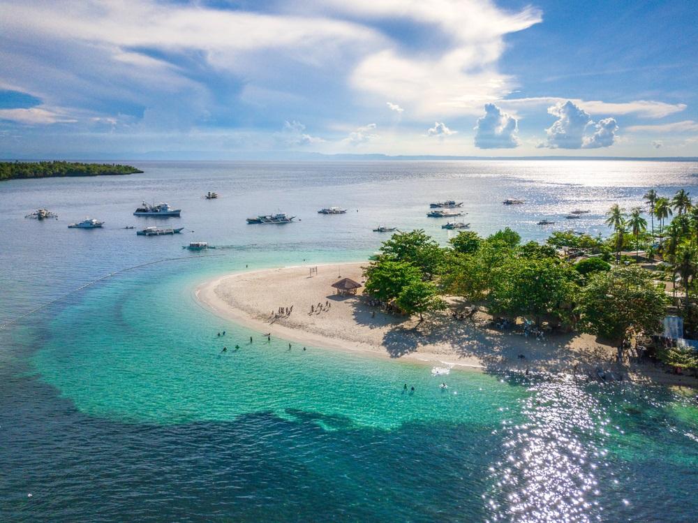 Luchtfoto van een eiland nabij Ceby stad. Azuurblauwe zee, donker en licht. Parelwit strandje en groene bomen rechts in het midden. Boten varen in de verte. Witte wolken en blauwe lucht io de achtergrond.