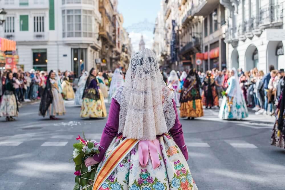 Locals in Valencia vieren het Fallas festival op straat in traditionele kledij. Op de voorgrond staat een vrouw met haar rug naar de camera, met een witte sluier op en een traditionele boljurk met gekleurde print. Ze houd een boeket vast met witte en roze bloemen.