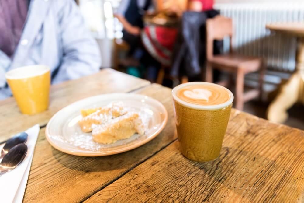 Zweden fika. Koffie met wat gebak in het café. Geserveerd op een houten tafel. Blurry mensen op de achtergrond.