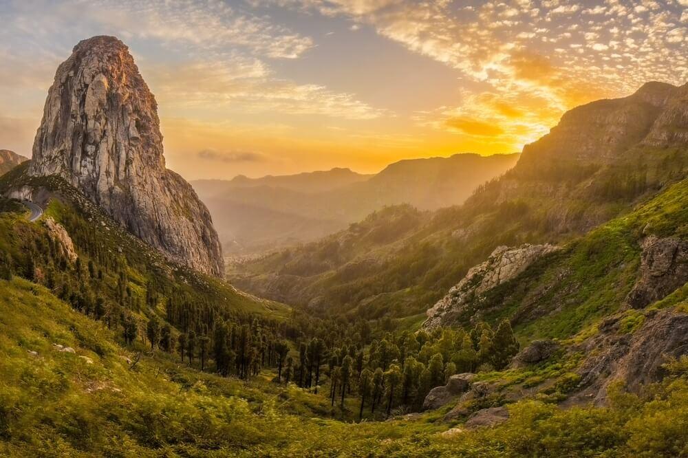 Roque Agando op het eiland Gomera in Spanje. Groene bergen en uitstekende rotsformatie. Ondergaande zon op de achtergrond.