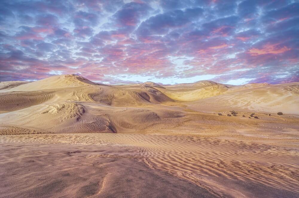 Zandduinen van de Great sandy desert in Australië. Paars gekleurde wolken boven de duinen.