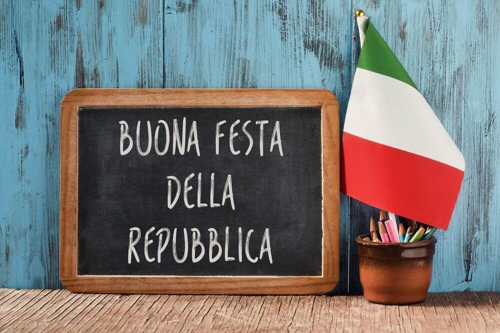 de tekst buona festa della repubblica, gelukkige republiekdag, de nationale dag van Italië, geschreven in het Italiaans op een schoolbord, en een vlag van Italië, op een rustieke houten tafel.