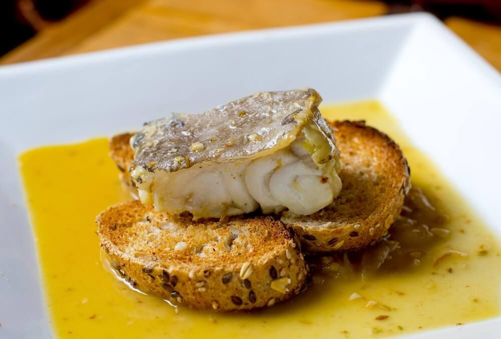 Pintxo met bacalao geserveerd op een wit bord met een oranje saus. 2 stukjes bruinbrood met zaadjes.