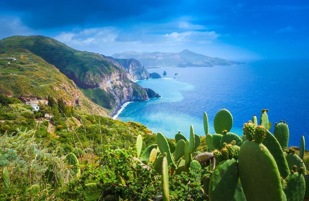 Lipari-eiland, Italië, prachtig uitzicht op het eiland Vulcano. Groene cactussen links in beeld, groene bergen en strakblauwe lucht.