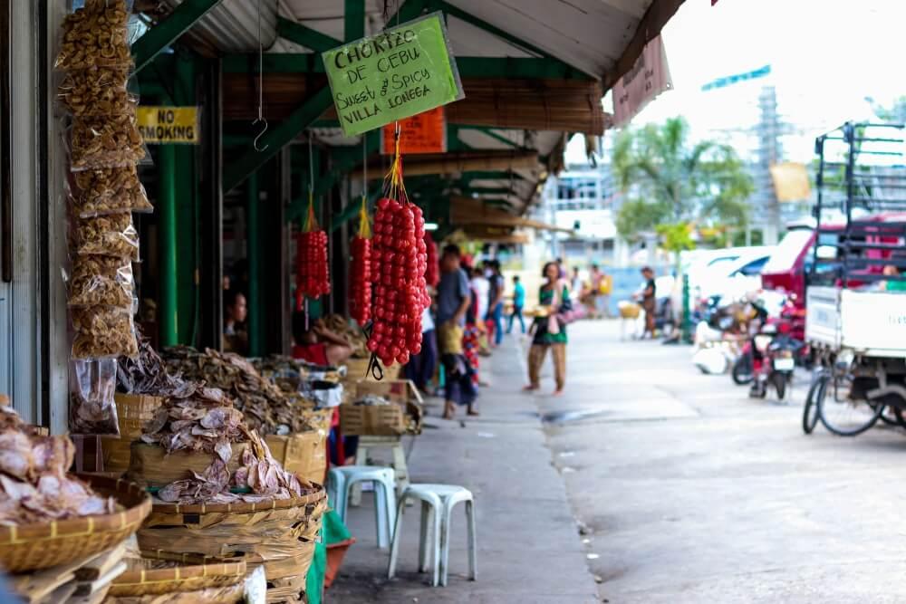 De lokale Taoban markt in Cebu stad, kraampjes met eten links voor. Groen papiertje met daarop chorizo de Cebu. Een aantal mensen staan in de verte.