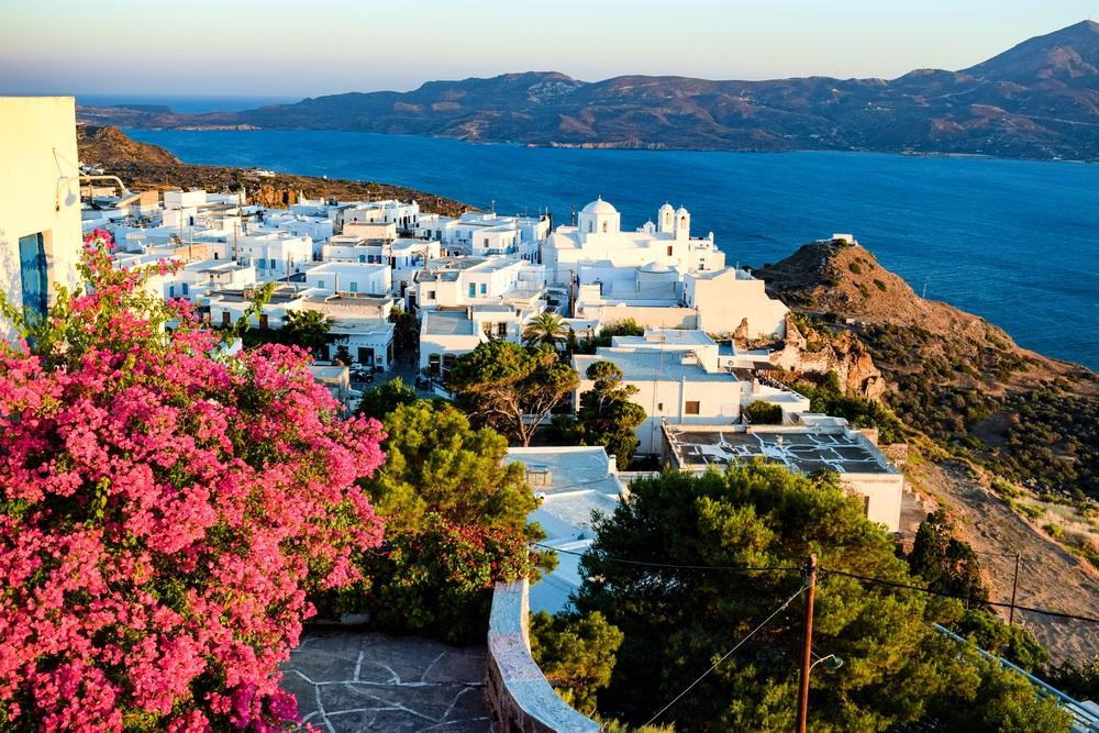 Het pittoreske witte dorpje Plaka op het eiland Milos, Azuurblauwe zee op de achtergrond en groene heuvels. Links een boom vol met roze bloemen.