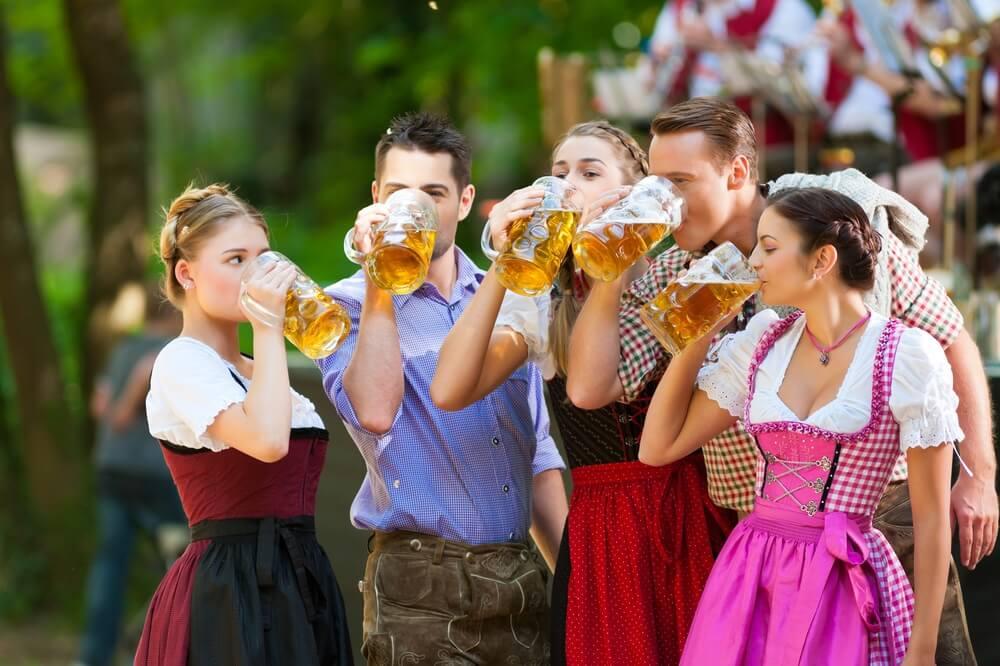 In de biertuin in Beieren, Duitsland - vrienden in Tracht, Dirndl en Lederhosen staan voor een band, drinken grote pullen bier.