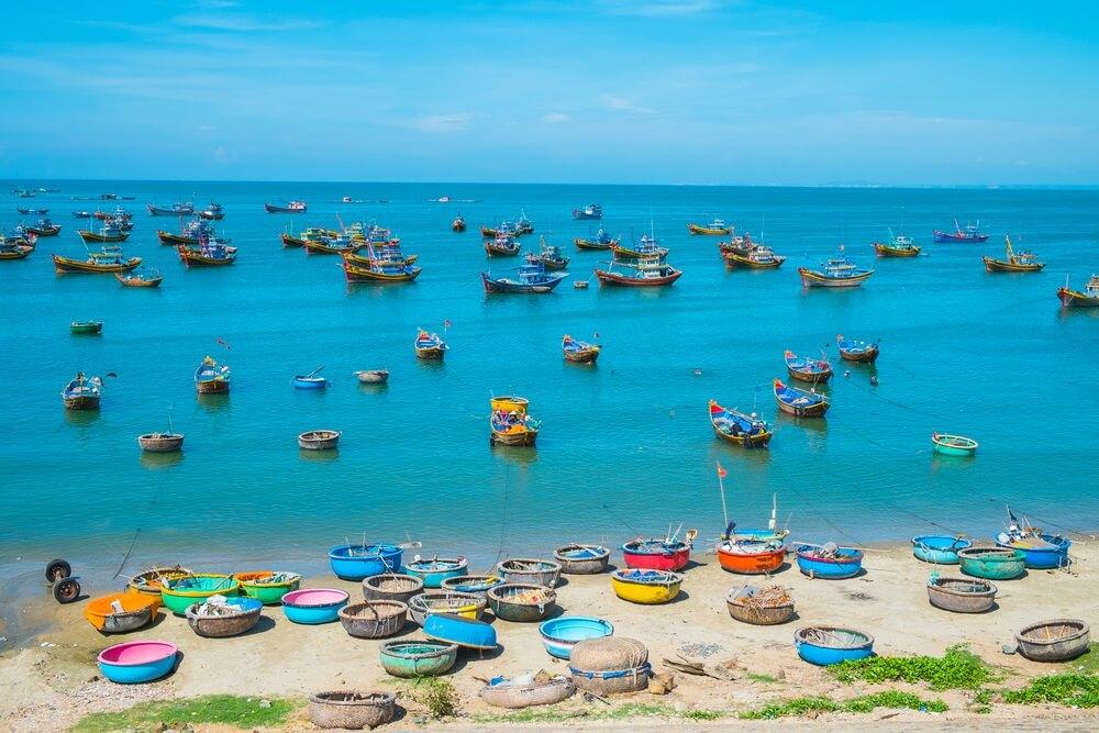 Kust van Mui Ne, met tientallen gekleurde vissersbootjes op het water en op het strand. Felblauwe lucht op achtergrond.