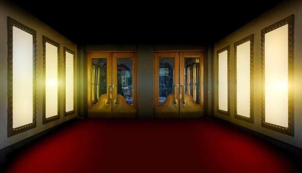 De ingang van een oud theater in Stockholm. Rode loper met aan weerszijden 3 lichte ramen. 2 gouden deuren in het midden.