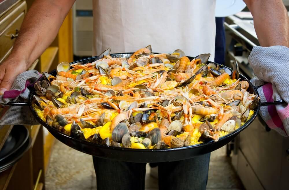Chef-kok draagt een vers bereide zeevruchtenpaella gekookt in een baskische gastronomische samenleving in San Sebastian.