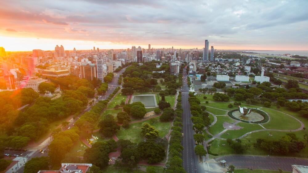 De wijk Palermo in Buenos Aires vanuit de lucht. Groene parken, skyscrapers en wegen zijn zichtbaar. Op de achtergrond grijze wolken en oranje gloed van ondergaande zon.