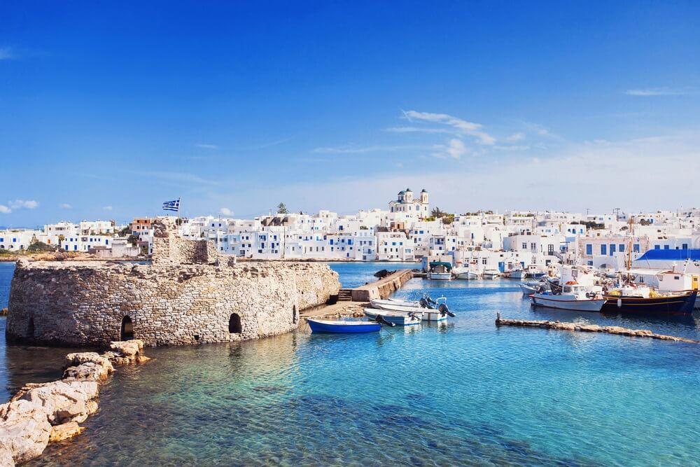 Schilderachtig wit Naousa-dorp, Paros-eiland, Cycladen, Griekenland.  Azuurblauwe zee op de voorgrond, strakblauwe lucht met enkele wolkjes.