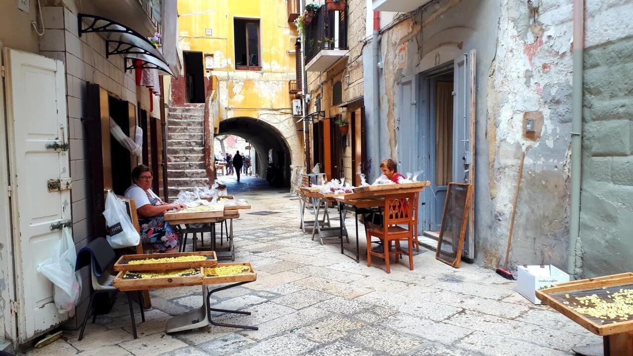 Smal steegje in Bari waar oude vrouwtjes aan de kant zitten om verse pasta te maken.