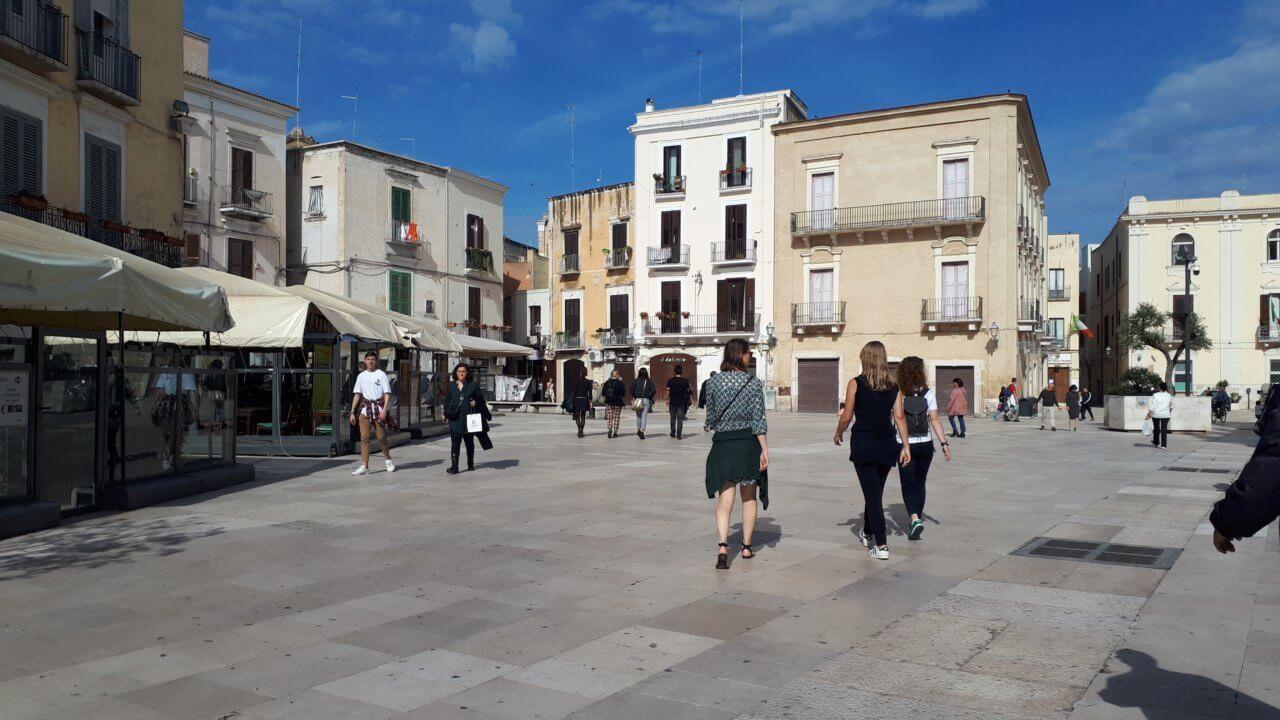 Het piazza Mercantile in Bari, mensen lopen op het plein langs de omliggende terrasjes. Strakblauwe lucht op de achtergrond.