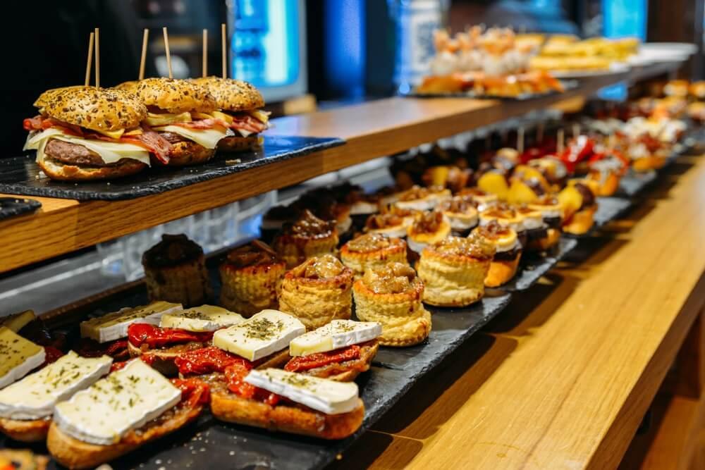 Traditioneel pintxos restaurant in San Sebastian, 2 rijen pintxos boven en onder elkaar op een houten plank.