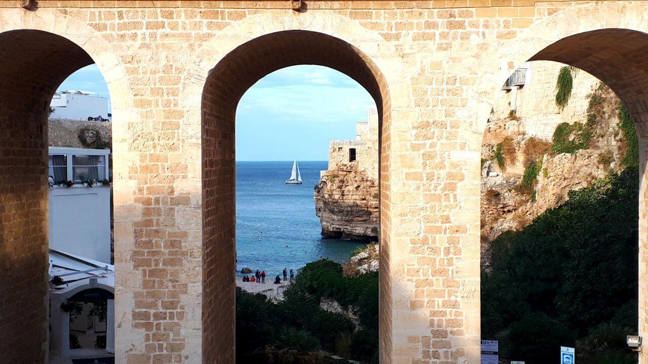 Het vissersstadje Polignano a Mare, bekeken door de gaten van een hoge brug met op de achtergrond de zee en een witte zeilboot.
