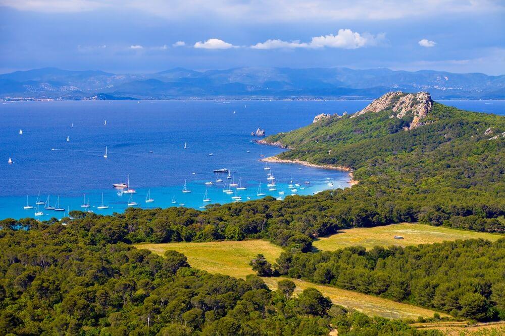 Luchtfoto van het eiland Porquerolles in Frankrijk. Groene bossen op de voorgrond, die uitlopen in een rotsformatie. Azuurblauwe zee met tientallen zeilbootjes en wazige, groene bergen op de achtergrond.