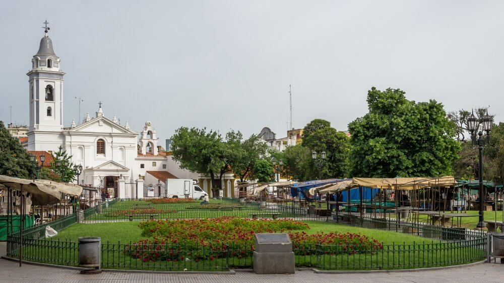 De wijk Recoleta in Buenos Aires met de beroemde, witte kerk op de achtergrond met daarvoor een groen parkje en aan zijkanten een markt.