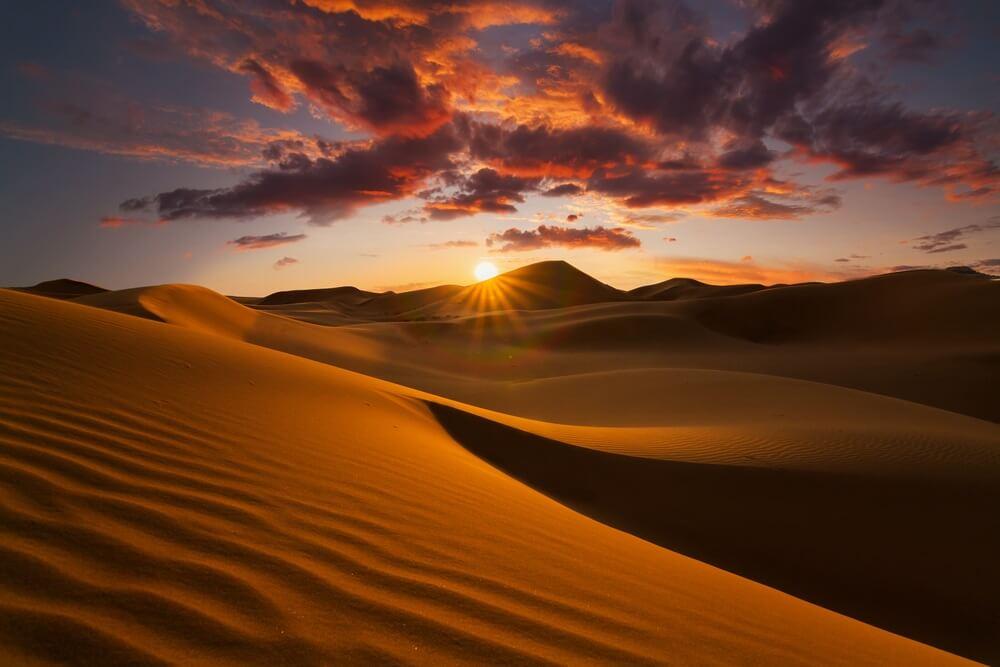 Prachtige zandduinen in de Sahara woestijn. Ondergaande zon achter de duinen, paarse lucht met roze gekleurde wolken.
