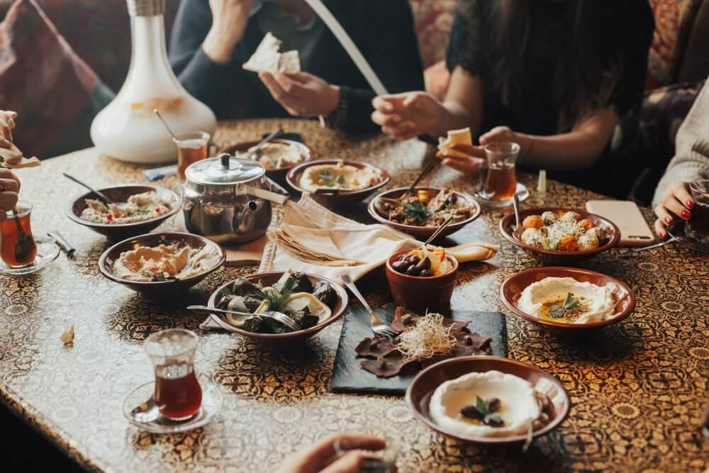 Gelukkig gezelschap van mensen in Libanon eten samen en roken shisha. Libanese keuken. Traditionele meze-lunch.