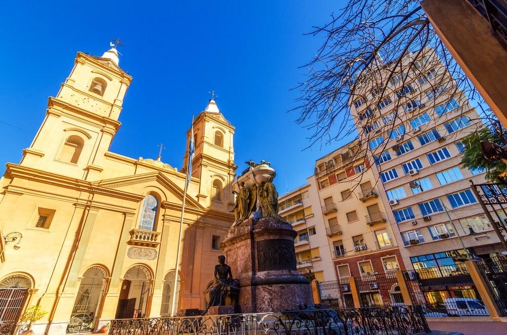 De wijk San Telmo in Buenos Aires met de bekende kerk aan de linkerkant, een standbeeld daarvoor en smalle, hoge gebouwen aan de rechterkant. Strakblauwe lucht daarboven.