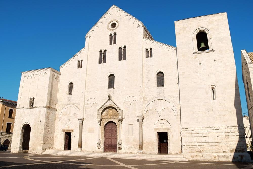De Sint Nicolaas Basiliek in Bari. Grote, witte kerk met op de achtergrond een strakblauwe lucht.