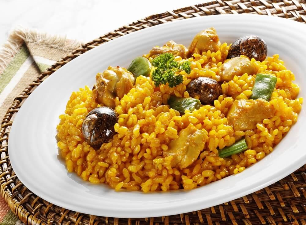 Bord vol met traditionele Spaanse paella, met 3 slakkenhuizen, konijn en een blaadje peterselie.