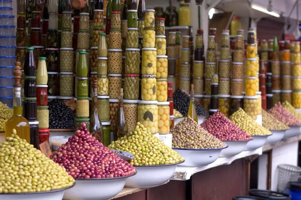 Verschillende soorten olijven en ingemaakte groenten en specerijen op een souk in Beirut. De ingemaakte groenten zijn hoog op elkaar gestapeld.
