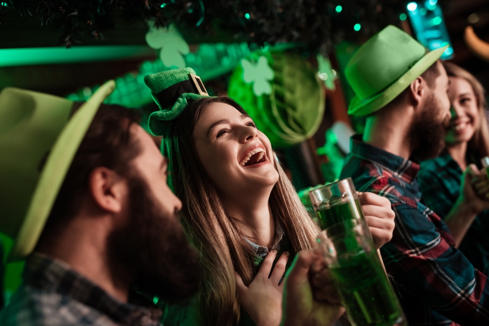 Jongeren vieren St. Patrick's Day. Ze hebben plezier aan de bar. Ze hebben hoofdeksels op en drinken bier.