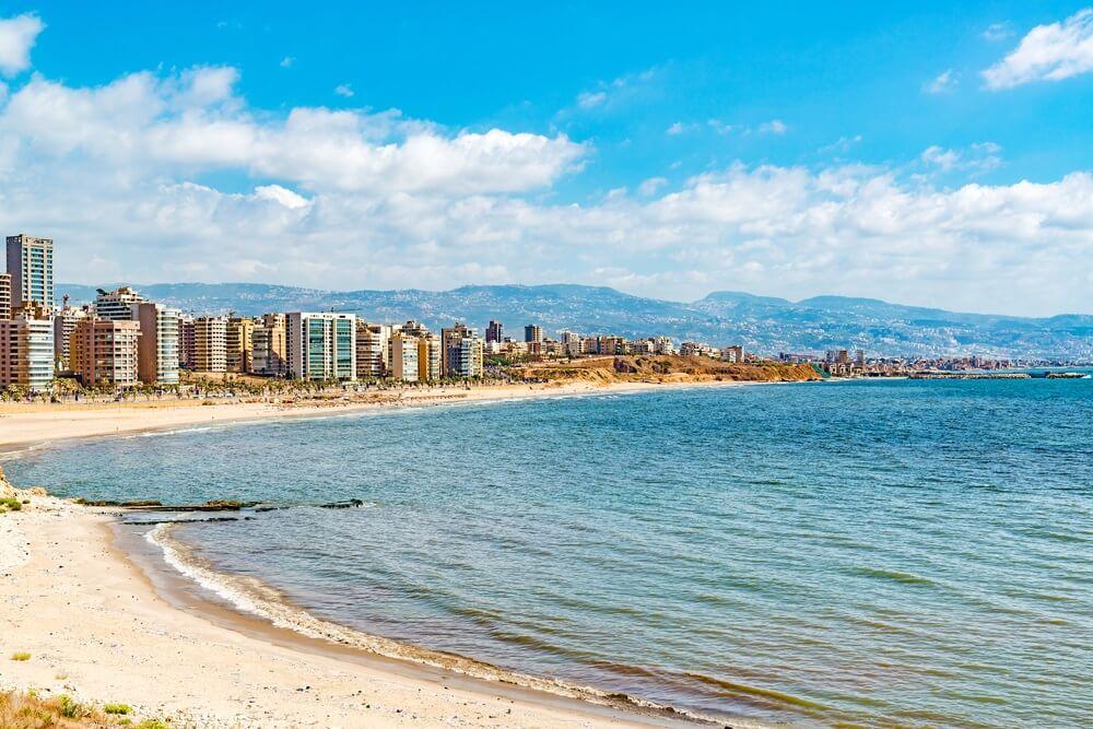 de kust van Beirut, met links een wit zandstrand en aan de horizon hoge gebouwen van de stad. Heuvels op de achtergrond en blauwe lucht met wolkjes.
