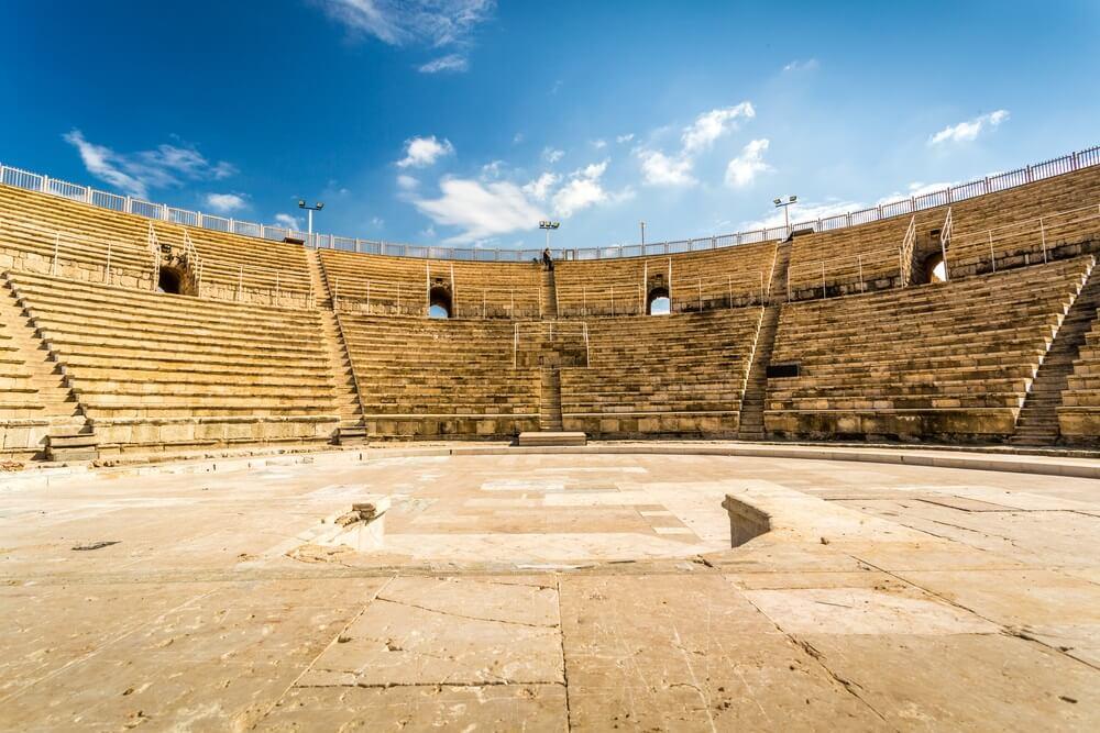 Het oude amfitheater in Caesarea met in het midden trappen en een grote stenen vloer daarvoor. Strakblauwe lucht op de achtergrond met enkele witte wolkjes.
