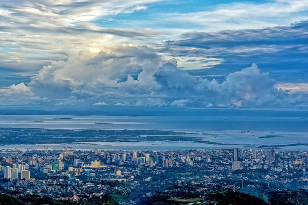 Panoramisch uitzocht over Cebu stad vanaf Tops Lookout. Alles is in een blauwe waas. De zee en wolken op de achtergrond.