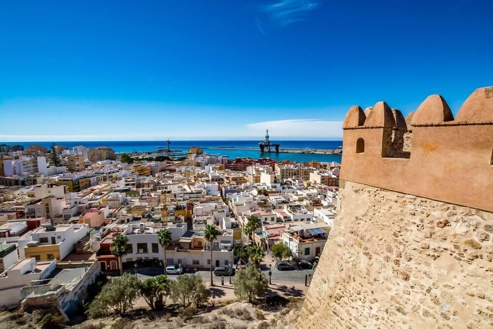 Uitzicht op Almeria stad en de oude haven vanaf het kasteel Alcabaza of Almeria. Links de toren van het Alcabaza. Strak blauwe lucht op de achtergrond.