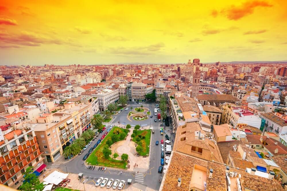 Luchtfoto van de stad Valencia met in het midden het centrale plein en daaromheen de stad. De lucht erboven is oranje en roze gekleurd.