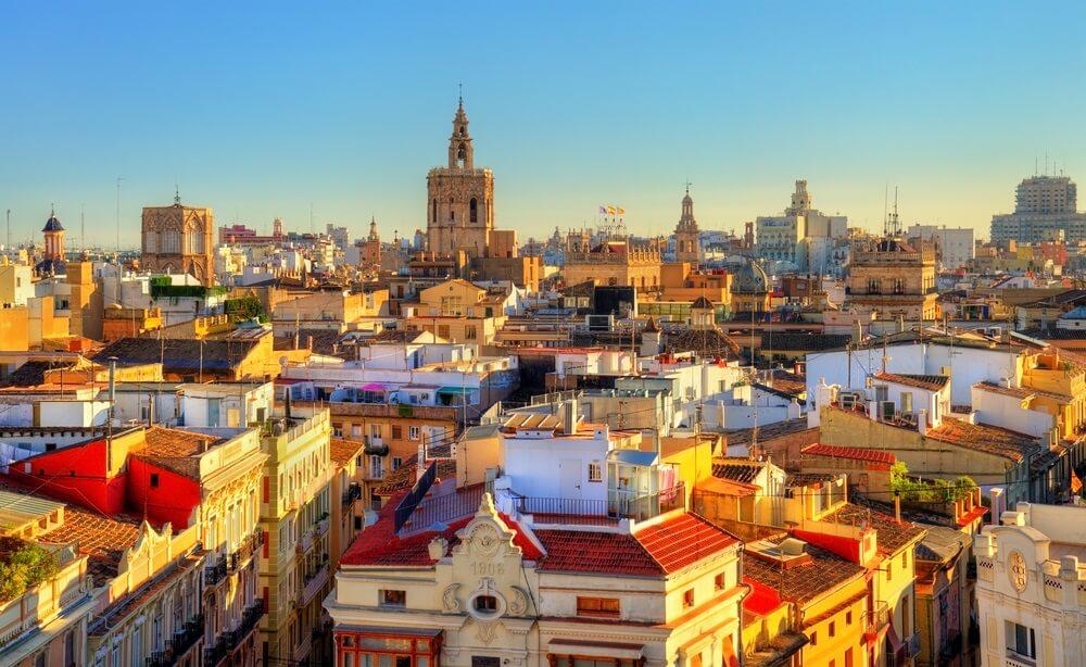 Uitzicht over de stad Valencia met zijn gekleurde gebouwen, kerken die uitsteken en een strakblauwe lucht daarboven.