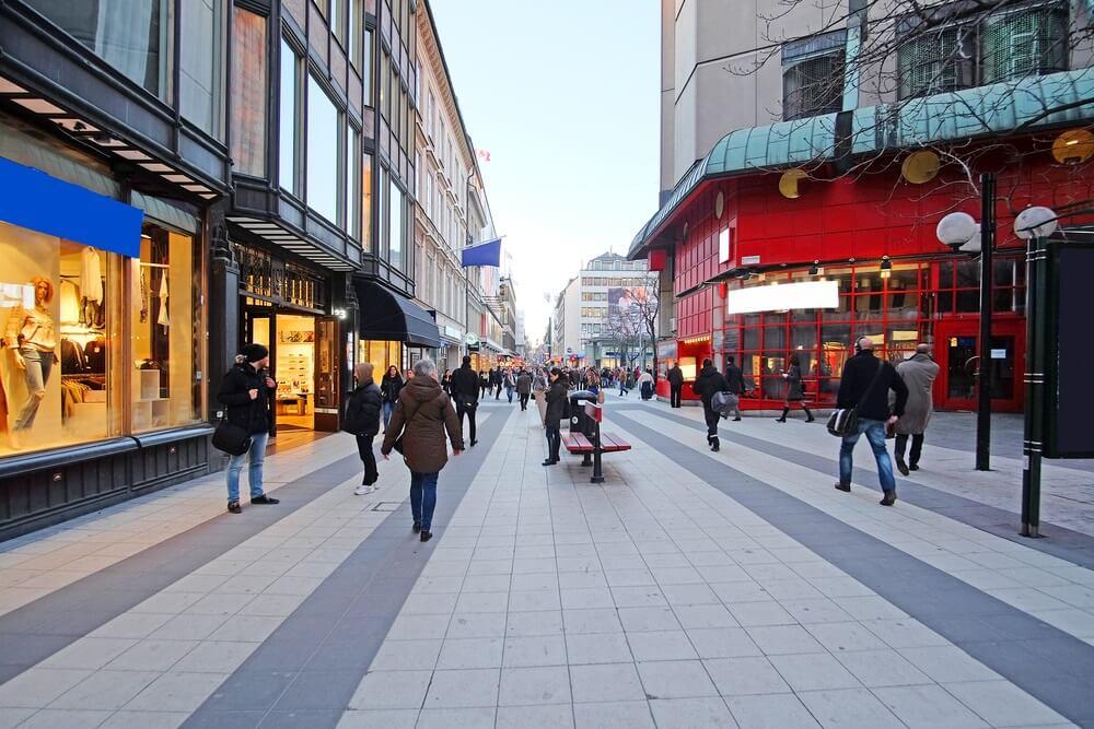 Winkelstraat in het centrum van Stockholm. Brede, rustige straat met enkele mensen. Winkels aan weerszijden.