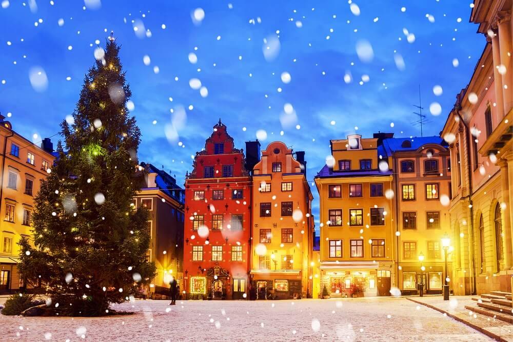Plein in Stockholm bedekt met sneeuw, links een kersboom en gekleurde huizen op de achtergrond. Sneeuwvlokken dwarrelen naar beneden.
