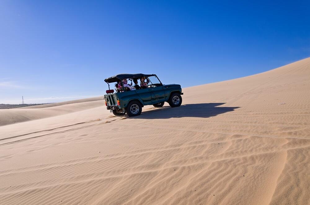 Witte zandduinen in Mui Ne, een jeep rijd in het midden en duin op. Strakblauwe lucht.