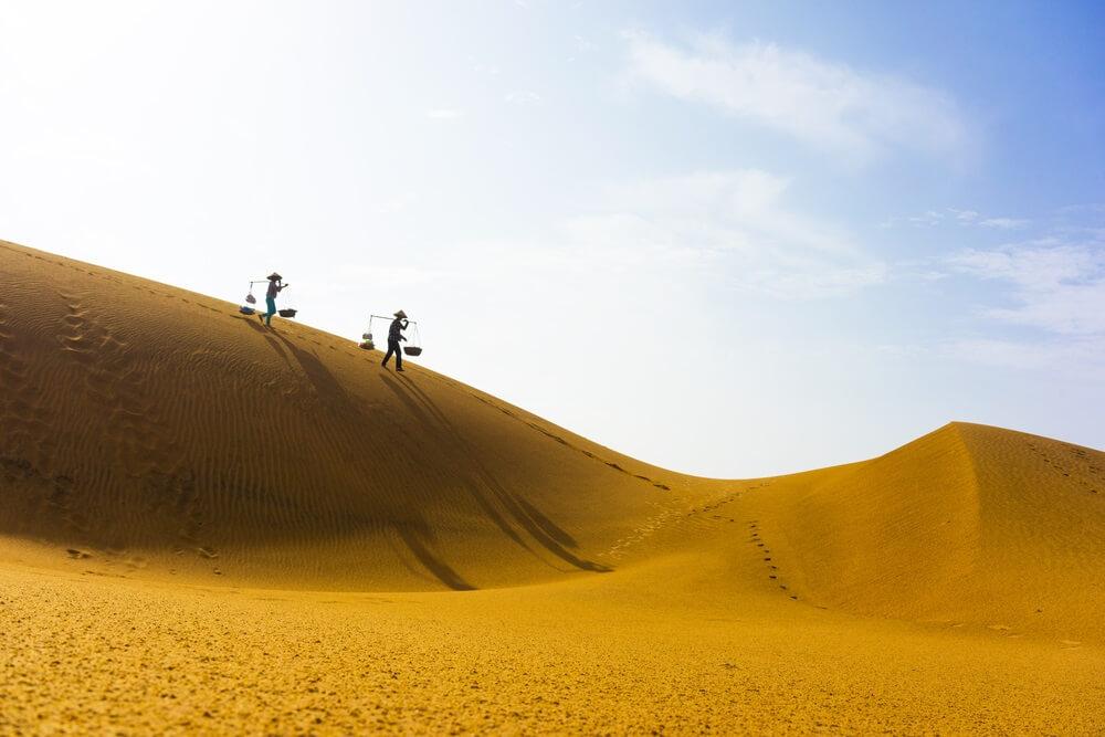 Zandduinen in Mui Ne, geelkleurig licht. Twee Vietnamezen lopen op de heuvel met eetmanden op hun schouders. Blauwe lucht met een paar wolkjes op de achtergrond.