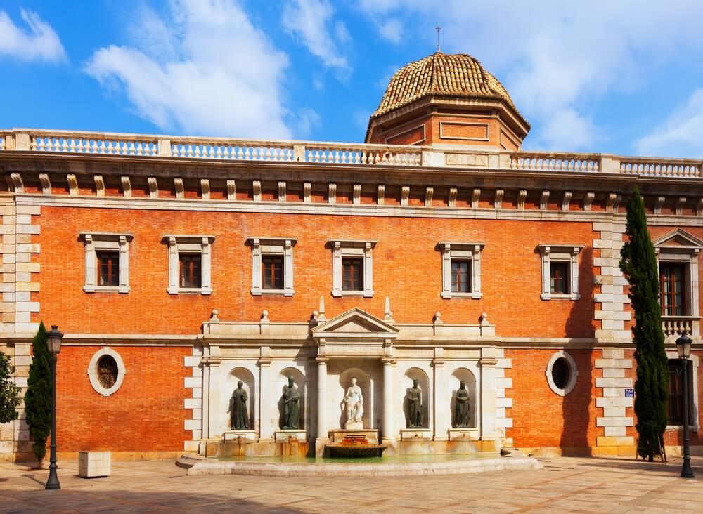 De kerk Colegio del Patriarca in Valancia, gebouwd met rode stenen en een witte kapel op de voorgevel.