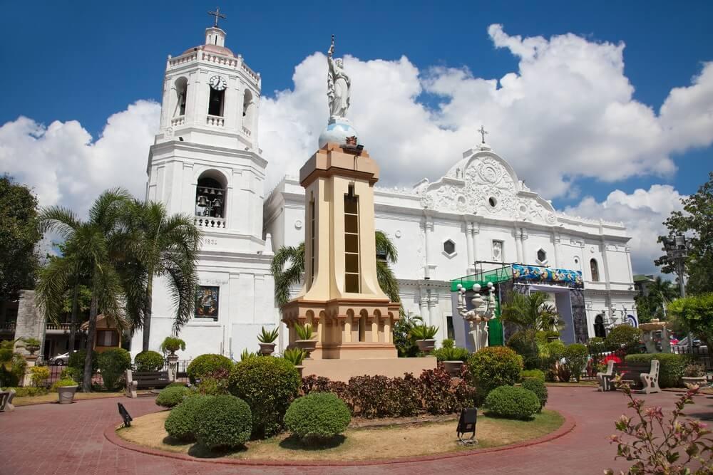 De Metropolitan kathedraal in Cebu stad, witte kerk met daarvoor een crème kleurig standbeeld met groene coniferen ervoor. Witte wolken met paar stukken blauwe lucht aan de horizon.