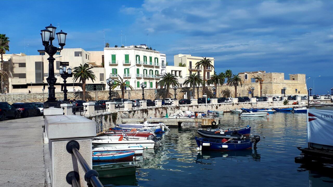 De boulevard van Bari met palmbomen aan de zijkant, de zee met vissersbootjes ernaast en gebouwen en een strakblauwe lucht op de achtergrond met enkele wolkjes.