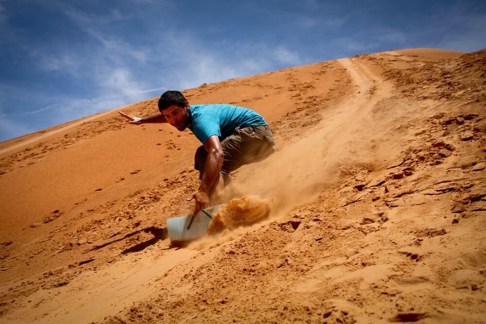 Rode zandduinen van Mui ne. met een man in het midden die aan het sandboarden is.