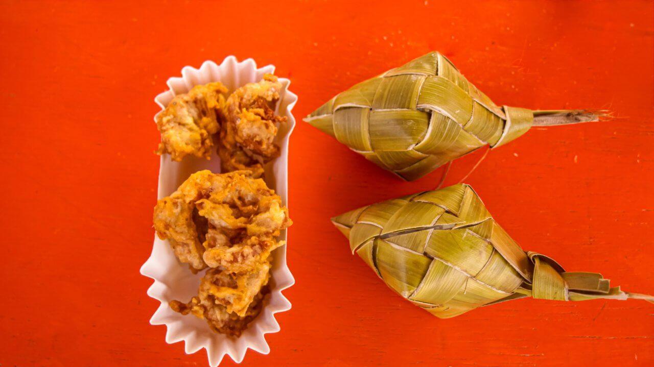 Twee streetfood gerechten uit Cebu stad, op een rode ondergrond. Links gefrituurde kip in een wit bakje, rechts tamales pakketjes.