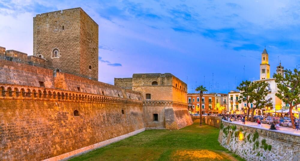 Het kasteel van Bari bij schemering. Links op de foto staat het kasteel, rechts de stad met pop de achtergrond de kathedraal. In het midden ligt een groen grasveldje.
