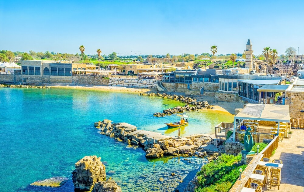 De oude haven van Caesarea, links de azuurblauwe zee en rechts terrasje en restaurants aan de boulevard. Strakblauwe lucht op de achtergrond en wat groene bomen.