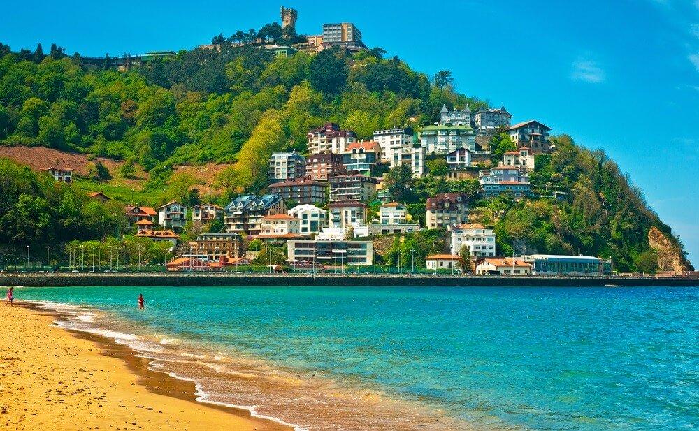 Het strand van San Sebastian met azuurblauwe zee, aan de overkant huizen gebouwd tegen een groene heuvel en een strakblauwe lucht.