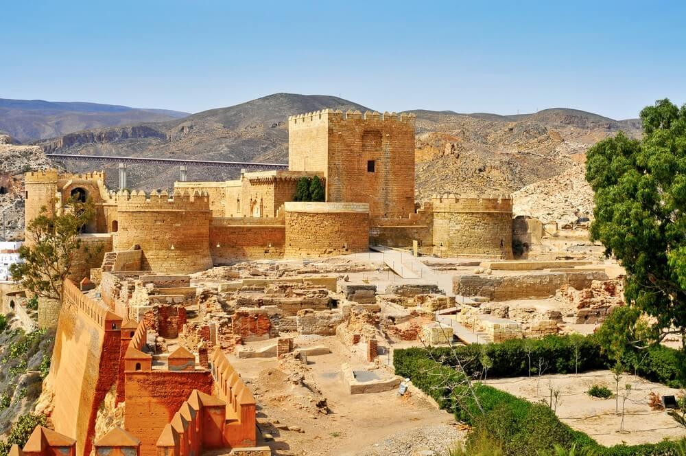 Het Alcazaba van Almeria, tegen groene heuvels aan. Strakblauwe lucht op de achtergrond.