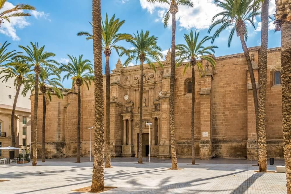 De imposante kathedraal van Almeria, op het centrale plein. Een tiental hoge palmbomen daarvoor en ernaast, blauwe lucht daarboven met enkele wolkjes.